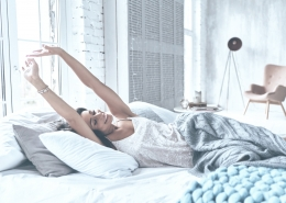 Attractive young woman smiling and stretching while lying on the bed at home